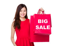 Woman hold with paper bag and showing big sale Royalty Free Stock Image
