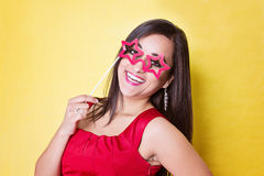 Woman hold photo booth prop red sun glasses. On yellow background Stock Photos