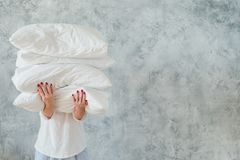 Woman hold pile white pillows bedding sleeping. Woman holding big pile of white soft cozy pillows on gray background. bedding and sleeping concept stock images