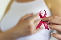 Woman hold pink ribbon for breast cancer awareness. Blurred background. Copy space available royalty free stock images