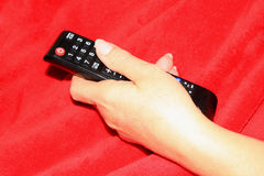 Woman hold's Tv remote control Stock Photo