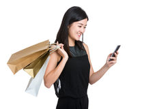Woman hold shopping bag and look at ceelphone Royalty Free Stock Photo