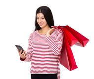 Woman hold with shopping bag and look at cellphone Royalty Free Stock Photo