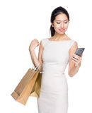 Woman hold with shopping bag and look at smartphone Stock Photos