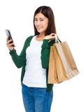 Woman hold with shopping bag and use of cellphone Stock Photography