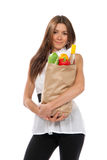 Woman hold shopping paper bag full groceries. Young woman hold shopping paper bag full of vegetarian groceries, red pepper, salad, bottle of dry wine, orange Royalty Free Stock Photo