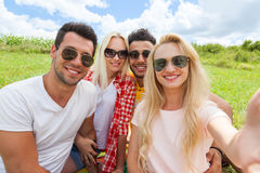 Woman hold smart phone camera taking selfie photo friends face close up picnic countryside Stock Image