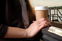 Woman hold takeaway cup of coffee on fence closeup. Stock Images