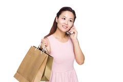 Woman hold talk to cell phone with shopping bag Stock Image