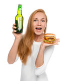 Woman hold tasty unhealthy burger sandwich in hand and bottle of Stock Images