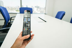 Woman hold TV remote control in meeting room table Royalty Free Stock Images