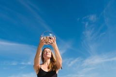 Woman hold up round aquarium with black fish stock photography