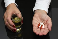Woman hold whiskey and pills in hands Stock Images