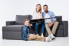 Woman holding acoustic guitar with family near by. And looking at camera stock image