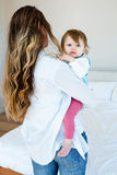 woman holding an adorable baby in a bedroom Stock Images