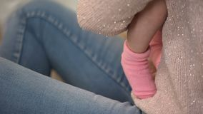 Woman holding adorable infant baby girl in pink socks, natural clothing for kids
