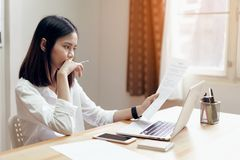Woman holding agreement documents and using laptop on table in office room, to plan advance budget. royalty free stock photo