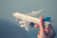 Close up of female hand holding white airplane toy model outdoor Royalty Free Stock Photography
