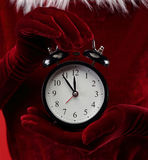 Woman holding alarm clock. Woman in christmas dress holding alarm clock royalty free stock images