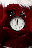 Woman holding alarm clock. Woman in christmas dress holding alarm clock royalty free stock image