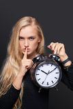 Woman holding alarm clock and gesturing hush Royalty Free Stock Photography