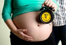 Woman is holding  alarm clock near her pregnancy belly Royalty Free Stock Photos