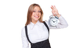 Woman holding alarm clock and smiling Royalty Free Stock Photos