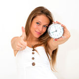 Woman holding alarm clock with thumbs up Stock Photography