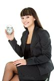 Woman holding alarm sitting on chair Royalty Free Stock Photo