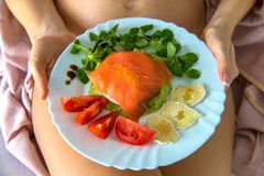 Detail of fit nude body woman hips holding healthy food plate in front, organic salmon topped by seaweed pearls french caviar stock images