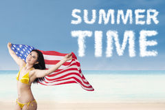 Woman holding american flag enjoying summertime. Young beautiful happy sexy woman holding american flag enjoying summer time at beach Stock Photos