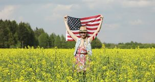 Woman holding American flag with pole, stars and stripe in a yellow rapeseed field. Female model is waving USA flag in the wind and smiling stock video footage