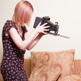 Woman holding antique camera. Young woman with blond hair delicately  holding an antique film camera with bellows Royalty Free Stock Image