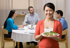 Woman holding appetizer and serving friends royalty free stock images