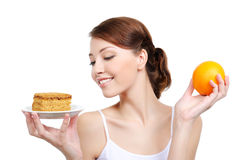 Woman holding appetizing cake and healthy orange. Young attractive woman holding appetizing cake and healthy orange Royalty Free Stock Image