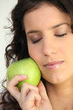 Woman holding apple against face royalty free stock photos