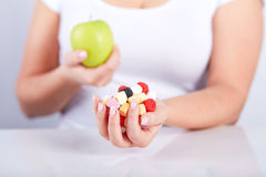 Woman holding apple and candies Royalty Free Stock Photos