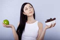 woman holding apple and chocolates Royalty Free Stock Images