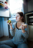 Woman holding apple and donut against fridge Stock Photography