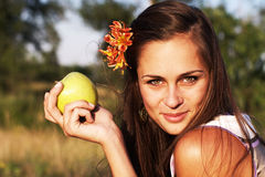 Woman holding apple with flower Royalty Free Stock Photography