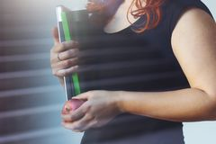Woman holding a apple and folder near window reflection stock images