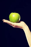 Woman holding an apple on hand. Stock Photography