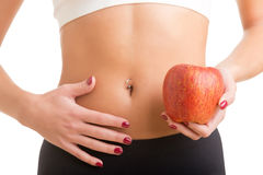 Woman Holding Apple. Woman holding an apple with a hand on her abdomen. Focus on the apple Stock Photo