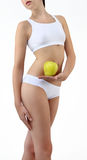 Woman holding an apple with his hands near the belly Stock Images