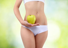 Woman holding an apple with his hands near the belly Royalty Free Stock Photography