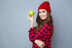 Woman holding apple and looking at camera. Portrait of a smiling young woman holding apple and looking at camera over gray background Stock Photo