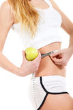 Woman holding apple and measuring her waist Royalty Free Stock Photography