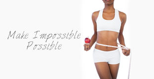Woman holding apple and measuring her waist Stock Photography