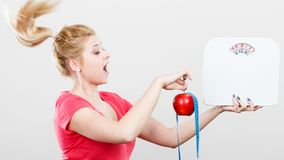 Woman holding apple,measuring tape and weight machine. Healthy fit lifestyle, getting ready for diet concept. Happy sporty woman with windblown hair holding red Stock Image