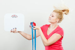 Woman holding apple,measuring tape and weight machine Royalty Free Stock Photos